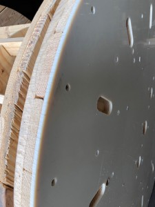 Wooden flange with smooth acrylic covering leaning against a regular wooden flange for comparison